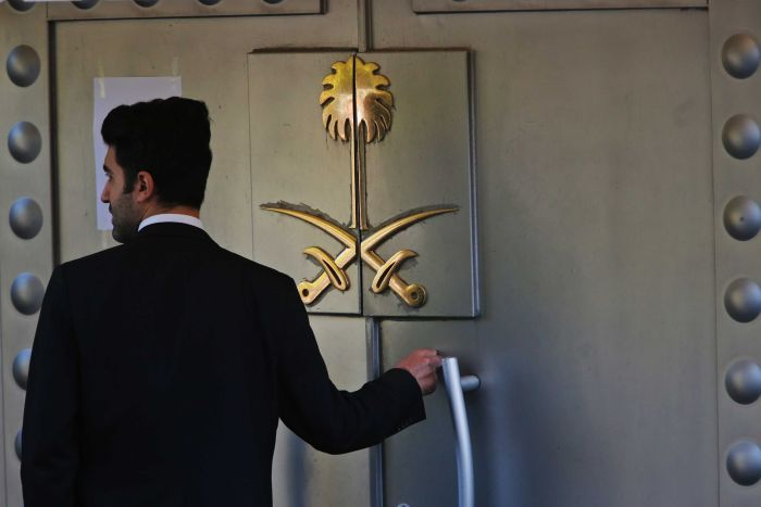 A security guard stands at the door, emblazoned with two crossed swords, to the Saudi Arabian consulate in Turkey.
