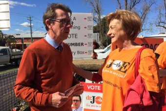A man in a tie and jumper chats to a constituent in a campaign shirt outside a polling station.