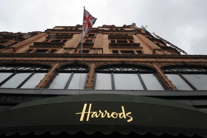 """An historical-looking building featuring a dark green awning features the word """"Harrods"""""""
