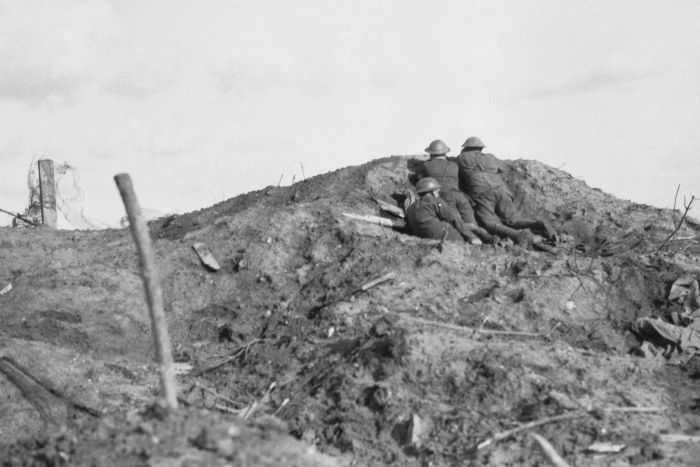 Black and white photo of troops on a muddy hillside.