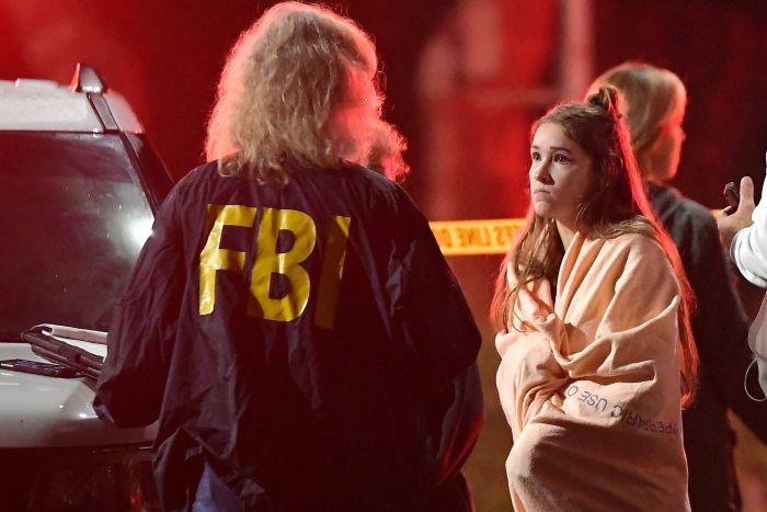 A young woman speaks to an FBI officer with red police lights flashing in the background after a mass shooting in California.