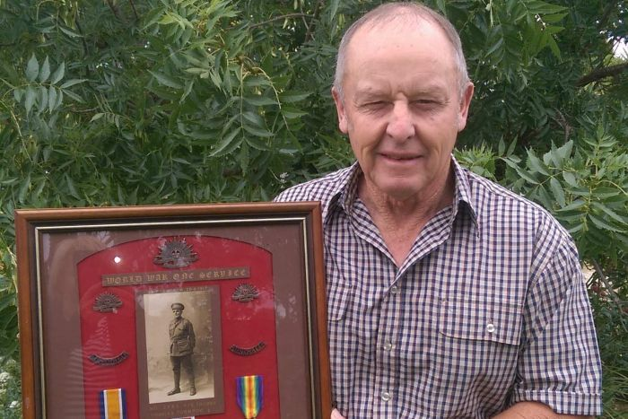 Ken in a background, holding a framed portrait and medals of Thomas Charles Townrow