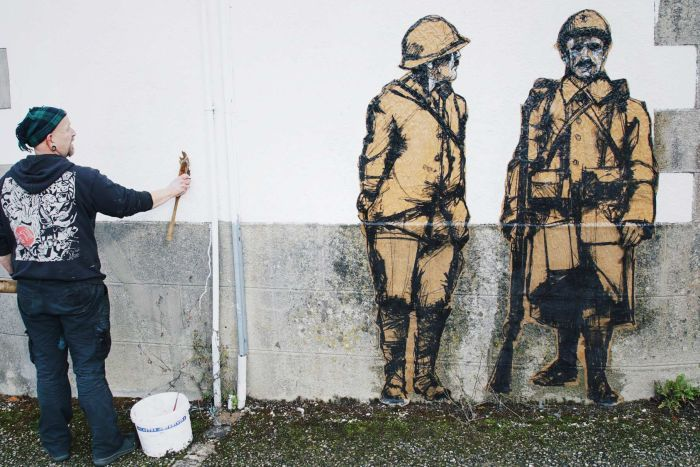 Guy Denning pastes up two of the posters on a wall in La Feuillee.