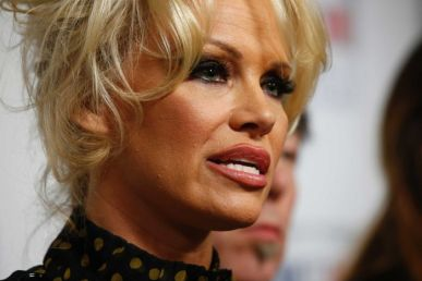 Headshot of Pamela Anderson, looking to the right of the image, mid-speech.