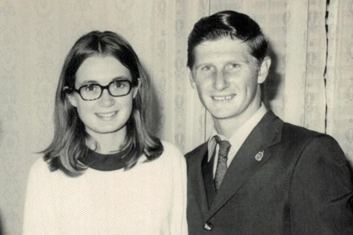 photograph of woman and man smiling at camera, man has hands around her waist