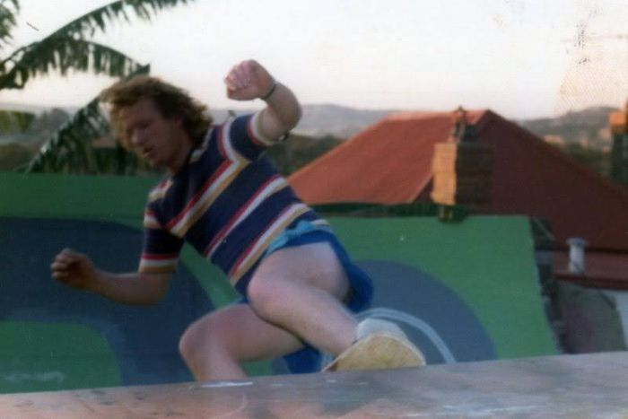 Bob Hastie skating up a ramp, wearing a striped t-shirt.