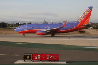 A blue, red and orange Southwest Airline plane sits on the tarmac in the background with blue skies in the backdrop.