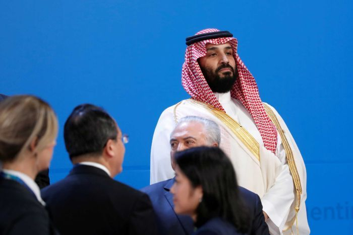Mohammed bin Salman watches on as world leaders arrive before the family photo is taken at the G20 Summit.