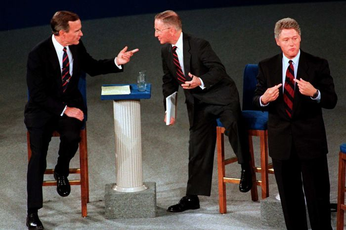 three men in suits on a stage on or near chairs