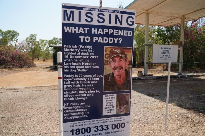 A poster with an image and details of a missing man is tied to a fencepost.
