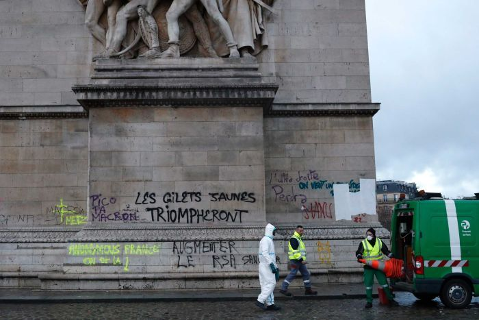 Parisian clean-up crews attend to the base of the graffitied Arc de Triomphe after riots