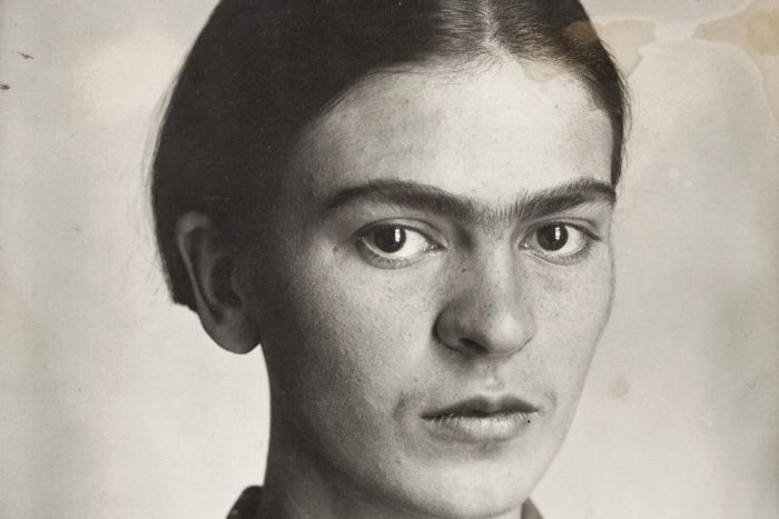 Frida Kahlo as a young girl stares out of black and white photograph at the viewer.