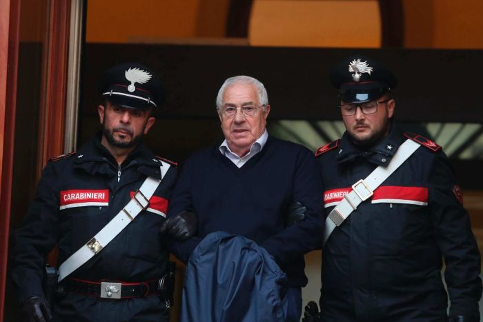 Two Italian police officers flank a handcuffed elderly man in glasses and a navy jumper.