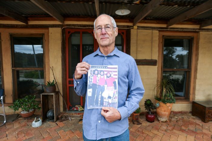 Bill Wigglesworth outside his house holding a picture of himself and two friends at an American Independence Day party.