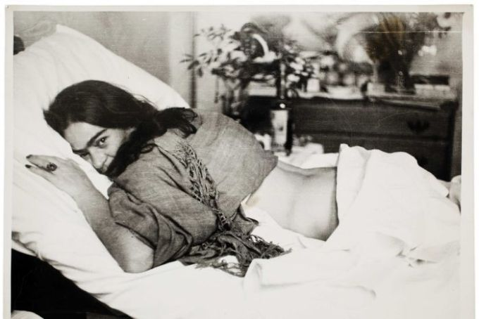Frida Kahlo lies face down on a bed, her head turned to look at the camera.