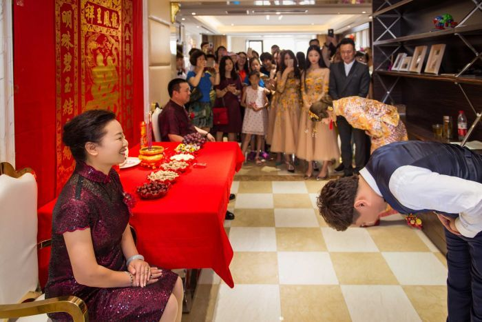 The groom and the bride bowed to their parents in front of a traditional Chinese style setting.