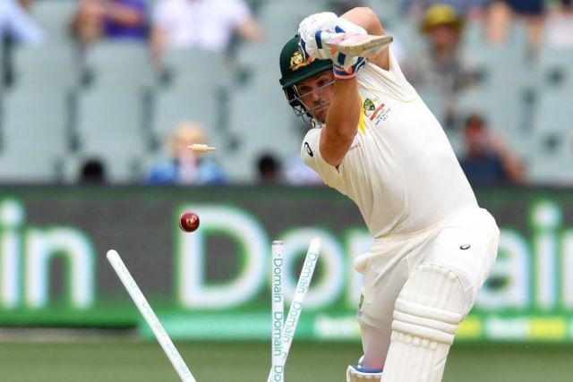 Aaron Finch plays a shot but misses the ball, which has split the stumps behind him