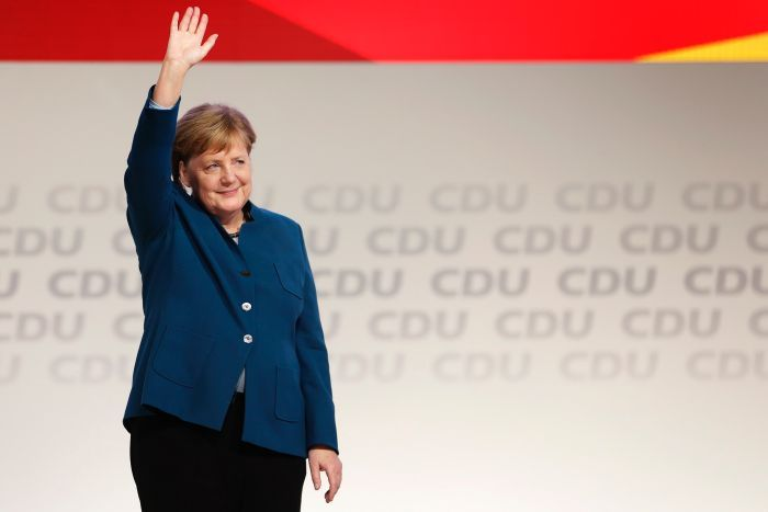 Angela Merkel stands on a stage in front of CDU signage. She waves to the crowd with a smile on her face.