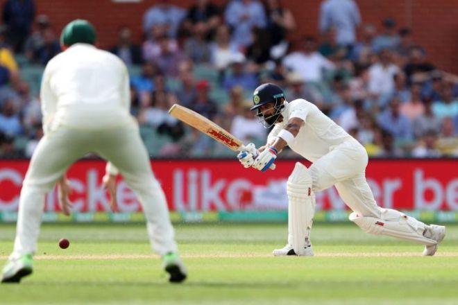 India batsman Virat Kohli plays a cricket shot as an Australian fielder looks on.