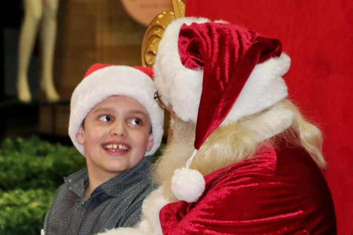 A boy in a grey shirt sits on Santa's lap on a big gold and red chair.
