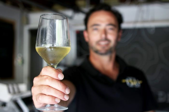 Joel Robinson holds a glass of mead out to the camera.