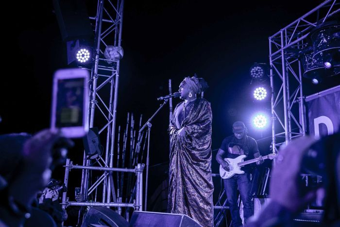 Colour photo of Zaachariaha Fielding of Electric Fields singing on stage at night time at Dance Rites 2018.