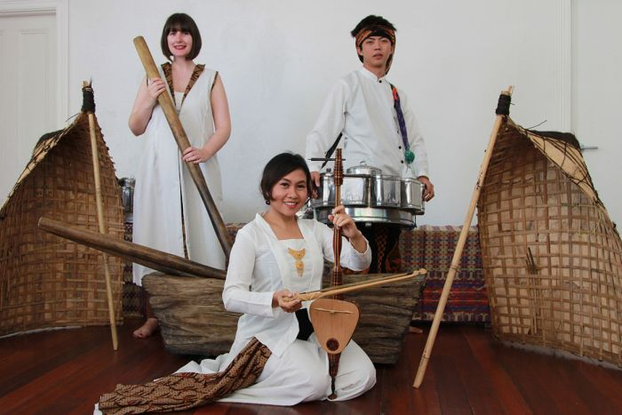 Bianca Gannon holds a timber rod, Luqmanul Chakim holds a large silver tin and Peni Candra Rini holds a timber string instrument