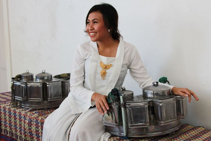 Indonesian singer Peni Candra Rini looks away from the camera and smiles.