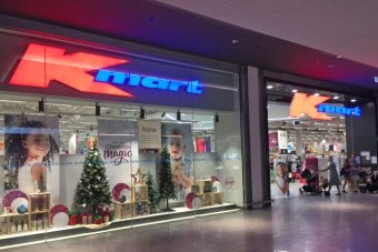 Shoppers enter and leave the Kmart store at Westfield North Lakes. There are christmas decorations in the window.