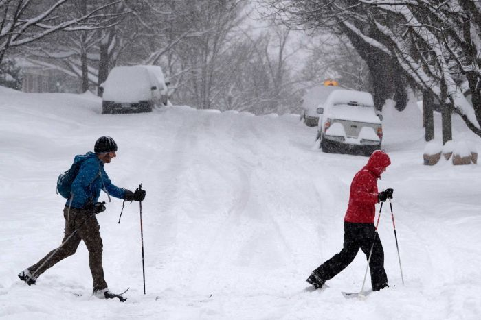 Two people in snow gear, with walking poles, trudge across a road covered in snow. The cars behind them are all but buried.