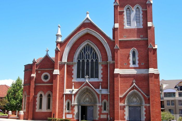 An exterior picture of a large brick Catholic Church with leadlight windows and white trim.