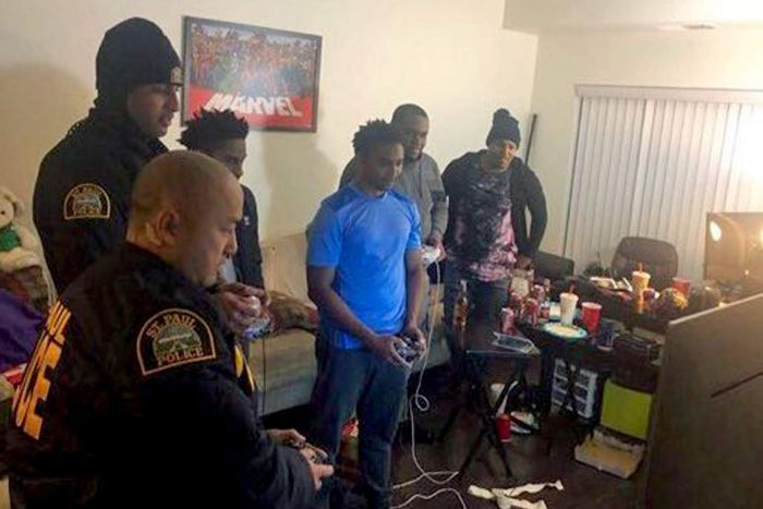 Two police officers stand with a group of gamers in front of a TV as they play a video game.