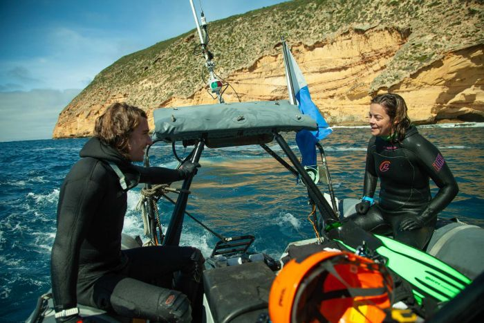 Two marine biologists sit on a rubber boat.
