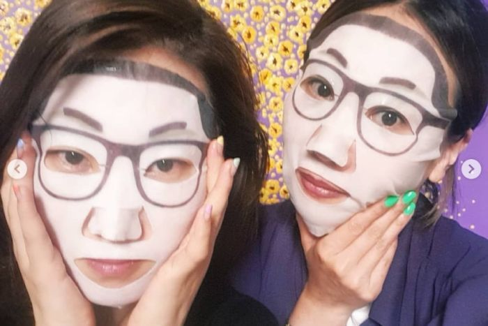 Two women wear the Kim Jong-un face masks, which have glasses and a strong hairline.