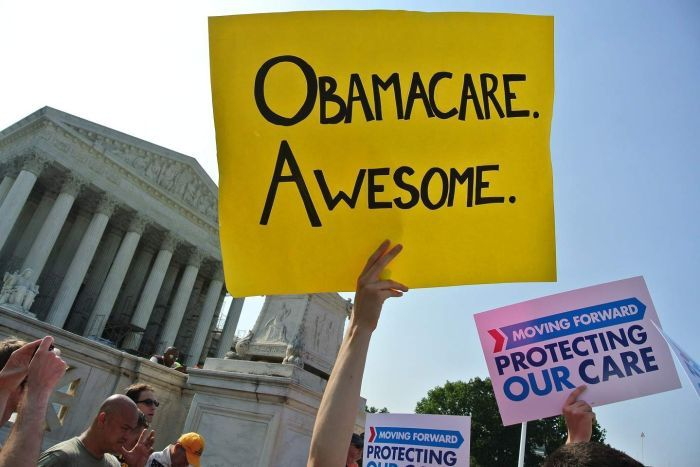 A bright yellow cardboard sign reads 'Obamacare. Awesome.' outside the US Supreme Court.
