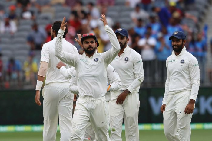 Virat Kohli throws his hands in the air, directing the crowd to get more animated during a cricket Test against Australia.