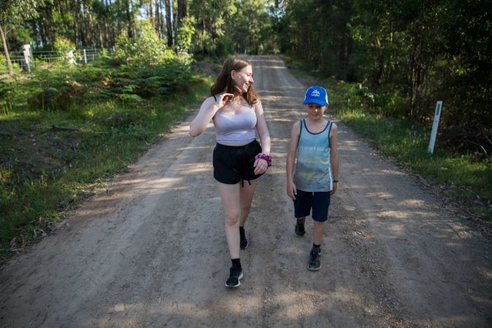 A teenage girl and younger boy are caught in a slice of sunlight as they walk towards the camera along a bush-lined dirt road.