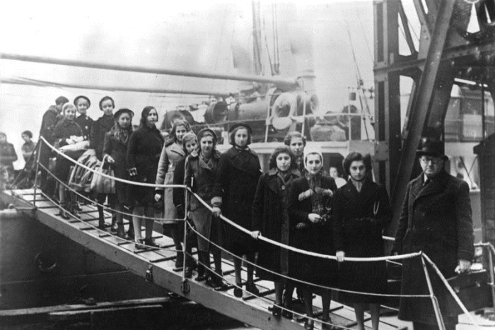 A group of young Jews stand on a drawbridge on a ship docked in London after being evacuated from Germany and Poland.