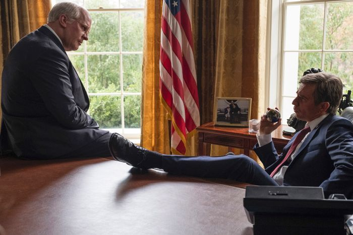 Colour still of Christian Bale sitting on corner of desk and Sam Rockwell in desk chair with leg up in 2018 film Vice.