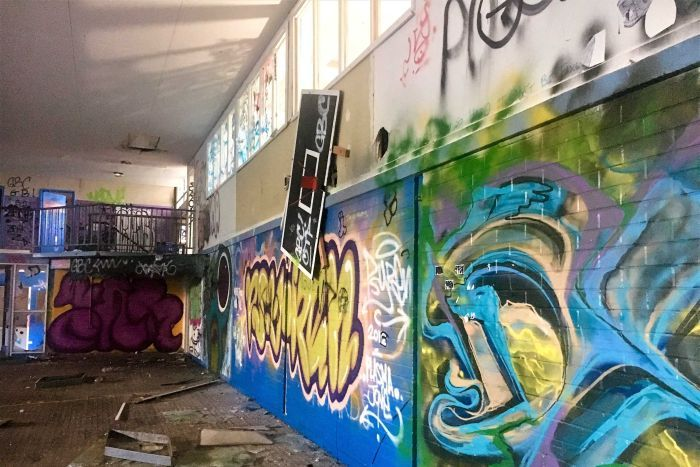 A vandalised room with graffiti covering walls, glass on floor and damaged basketball hoop.
