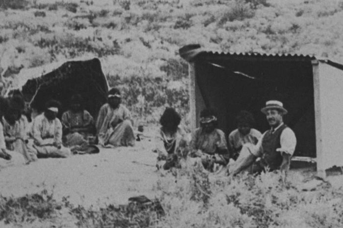 Photo of a group of indigenous patients sitting outside makeshift huts on the lock hospital islands, off the WA coast