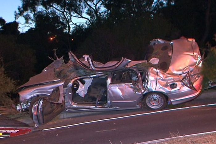 The wreckage of a silver Ford sedan after crashing into trees.