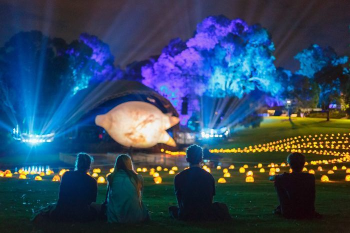 Four people sitting on grass at the Kings Park amphitheatre looking at a colourful light installation.