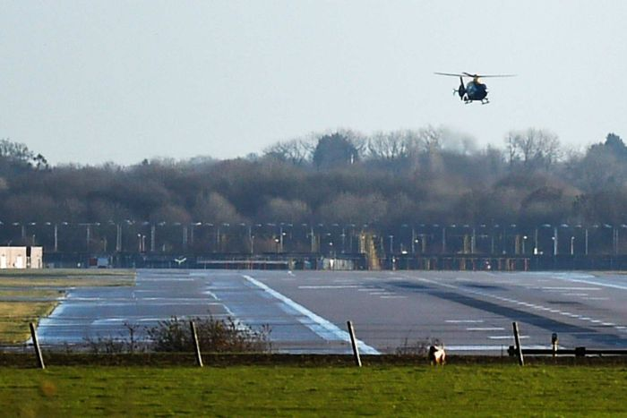 A dark-coloured helicopter hovers over an empty airport runway.