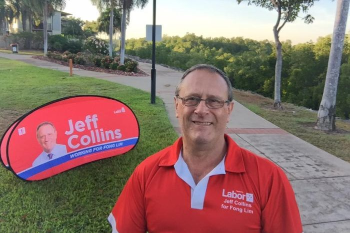 A man stands in a park in front of a political sign.