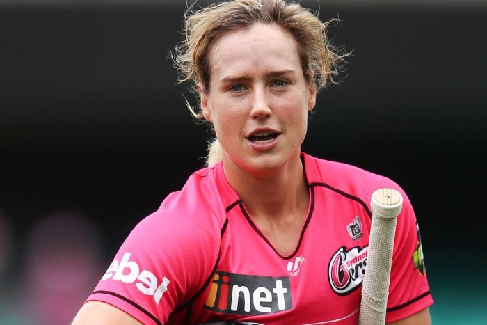Ellyse Perry carries her bat, gloves and helmet off the field.