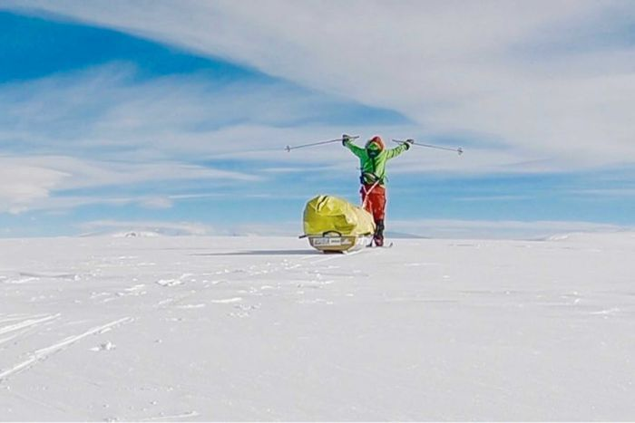 Colin O'Brady holds his ski poles in the air as he stands near his sled in the ice.