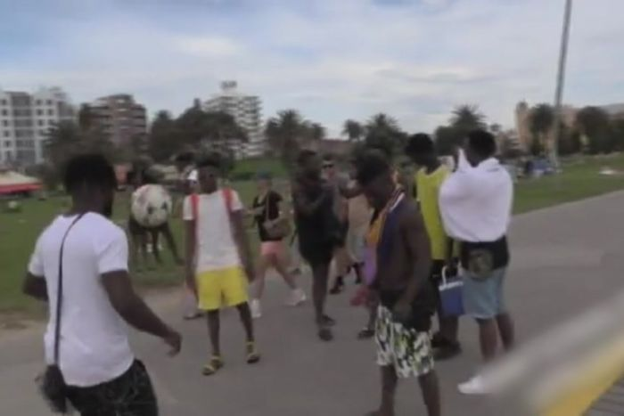 Young men kick around a soccer ball on the footpath next to the beach.