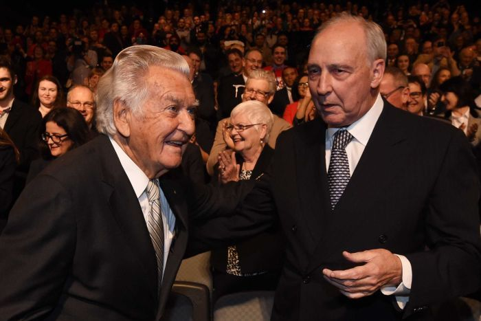 Paul Keating and Bob Hawke stand next to each other in suits