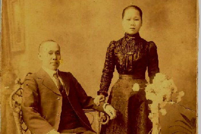 An old photograph of a man in a suit and a woman in a high-necked blouse holding a bunch of flowers
